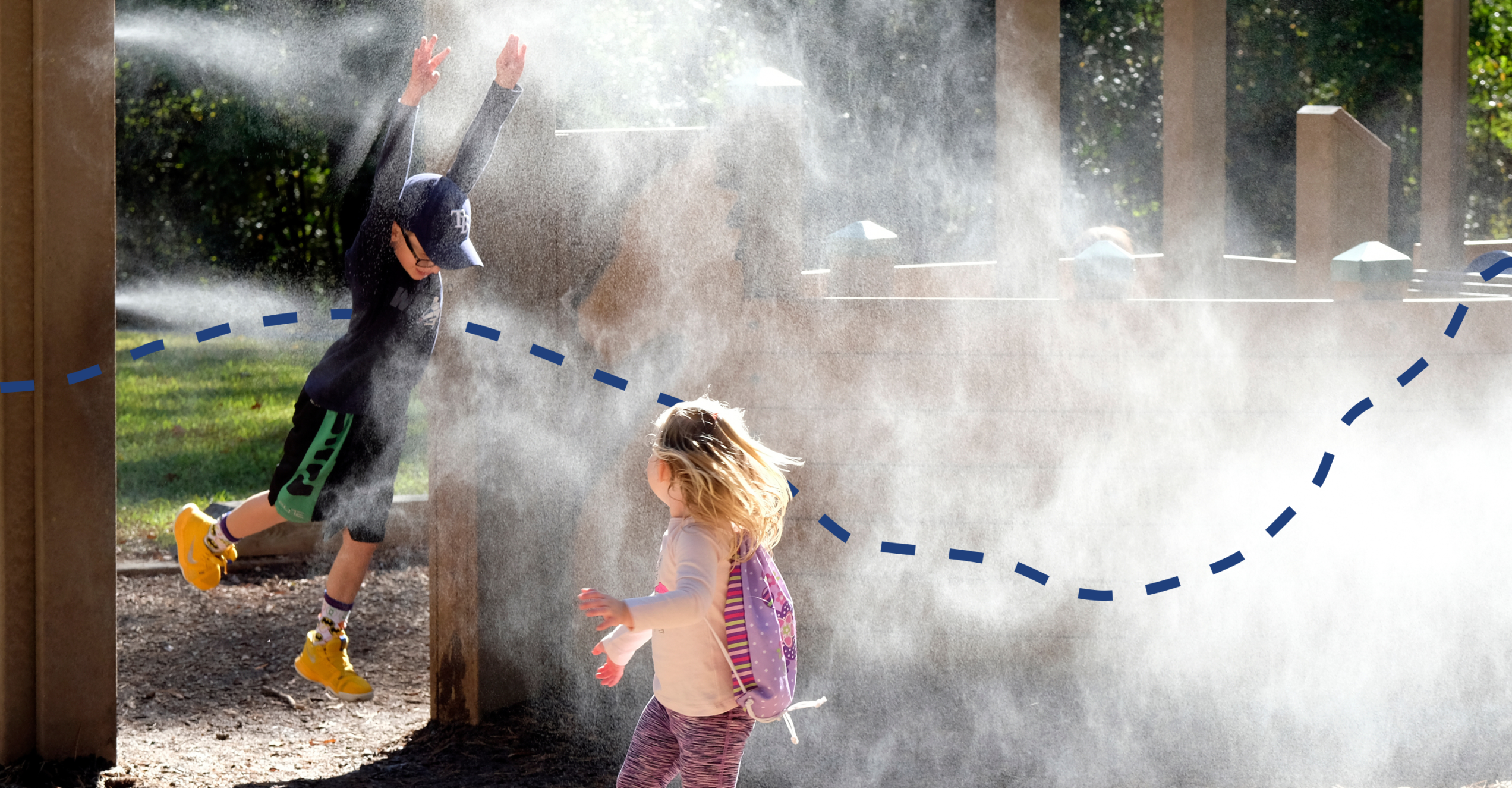 Two children playing in a mist station at a playground.