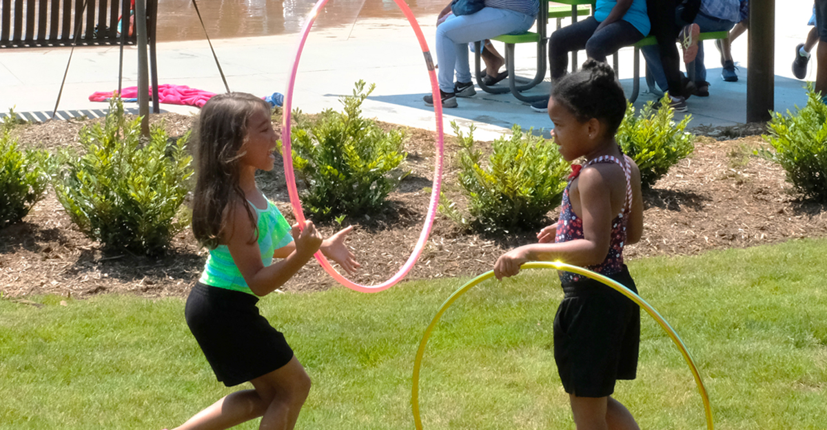 Two young girls playing with hula hoops in a park.