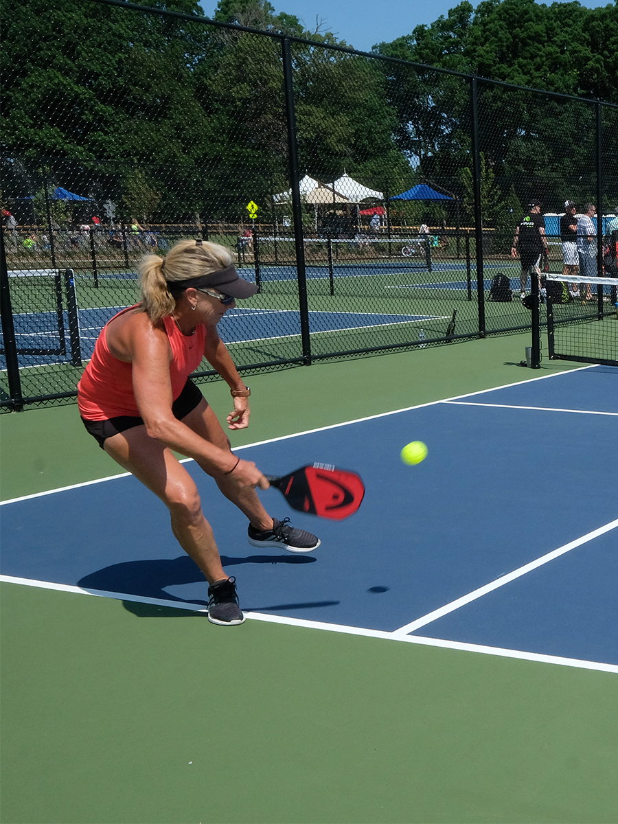 A woman playing pickleball on a blue court.