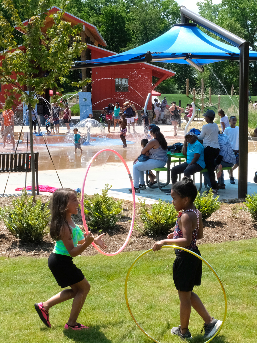 Two young girls playing with hula hoops in a park with several people in the background.