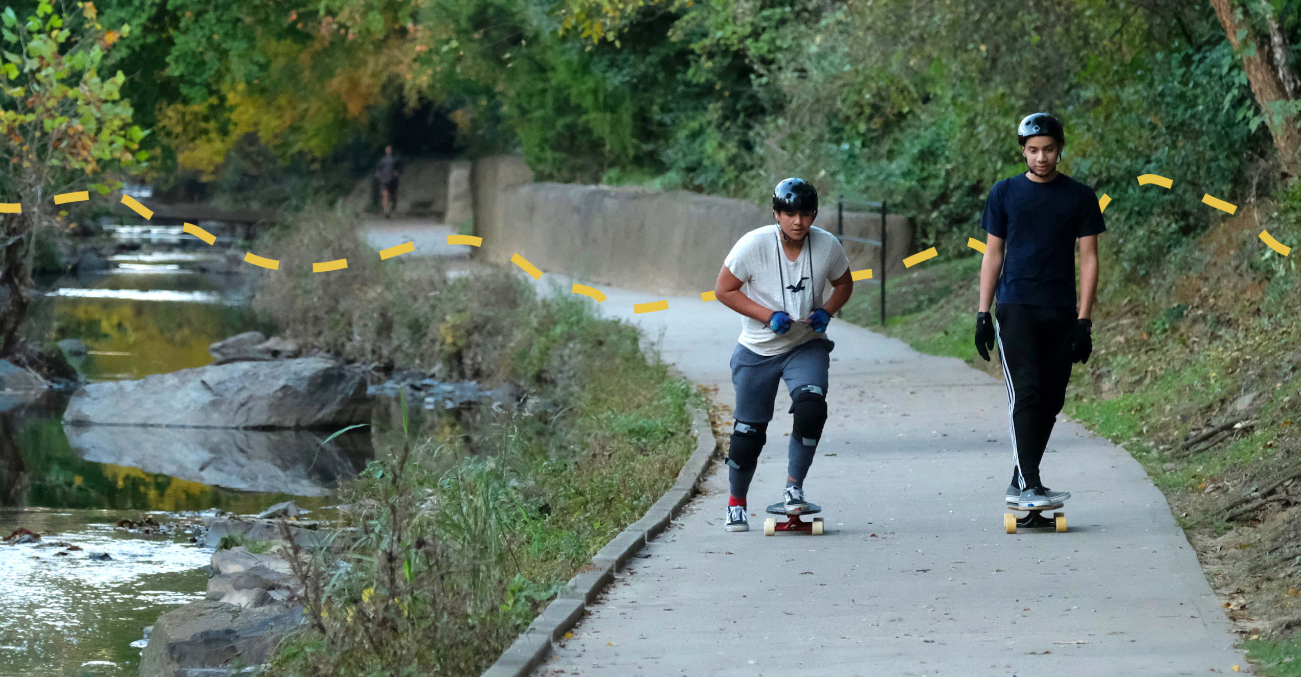 Two young men riding skateboards side by side on a paved path next to a creek.
