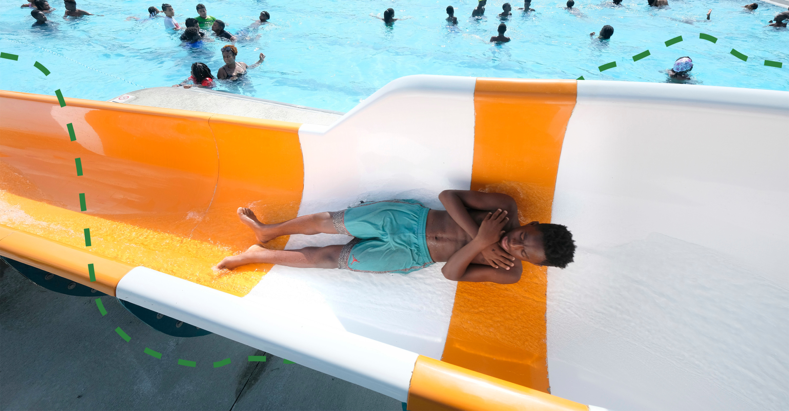 A young man riding down on an orange waterslide, with a swimming pool in the background.