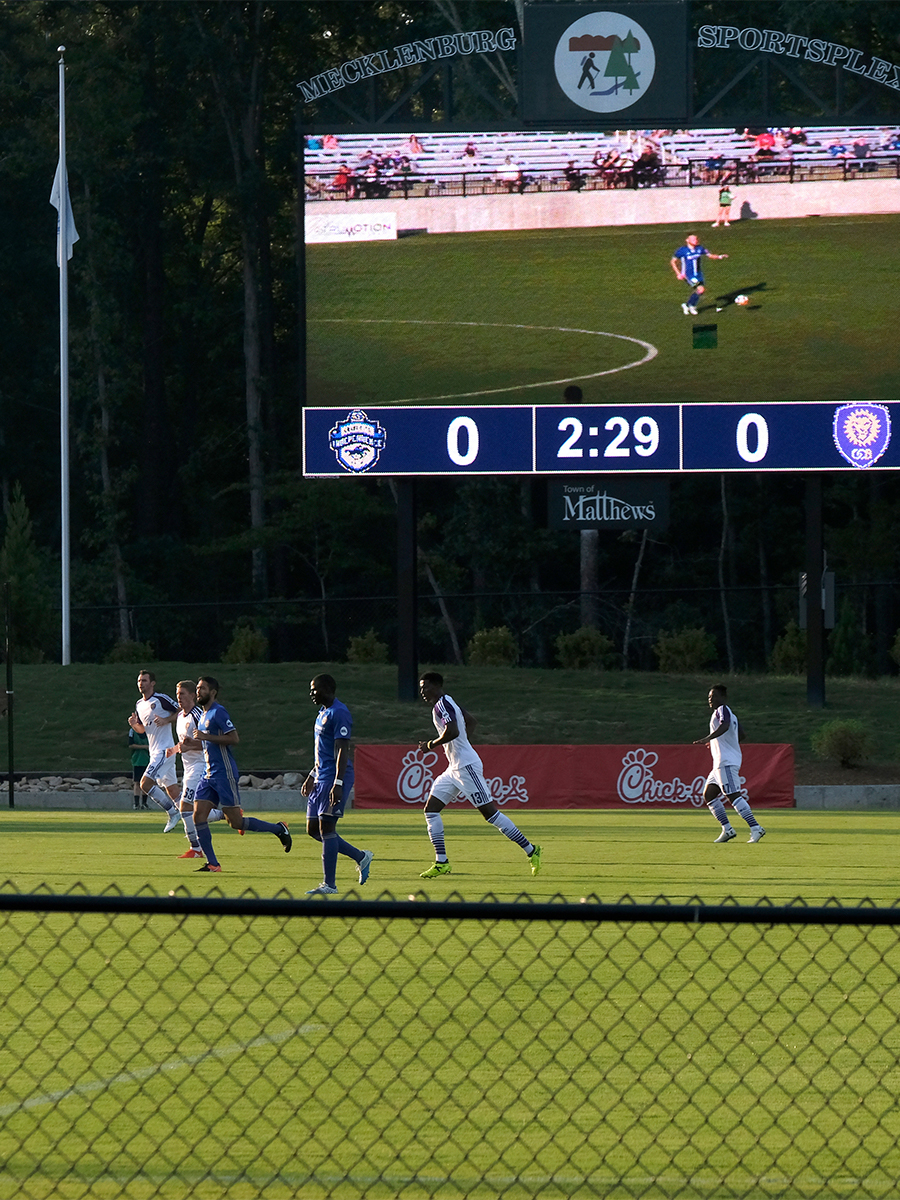 A Charlotte Independence soccer game. Soccer players are running on a green field with a scoreboard in the background.