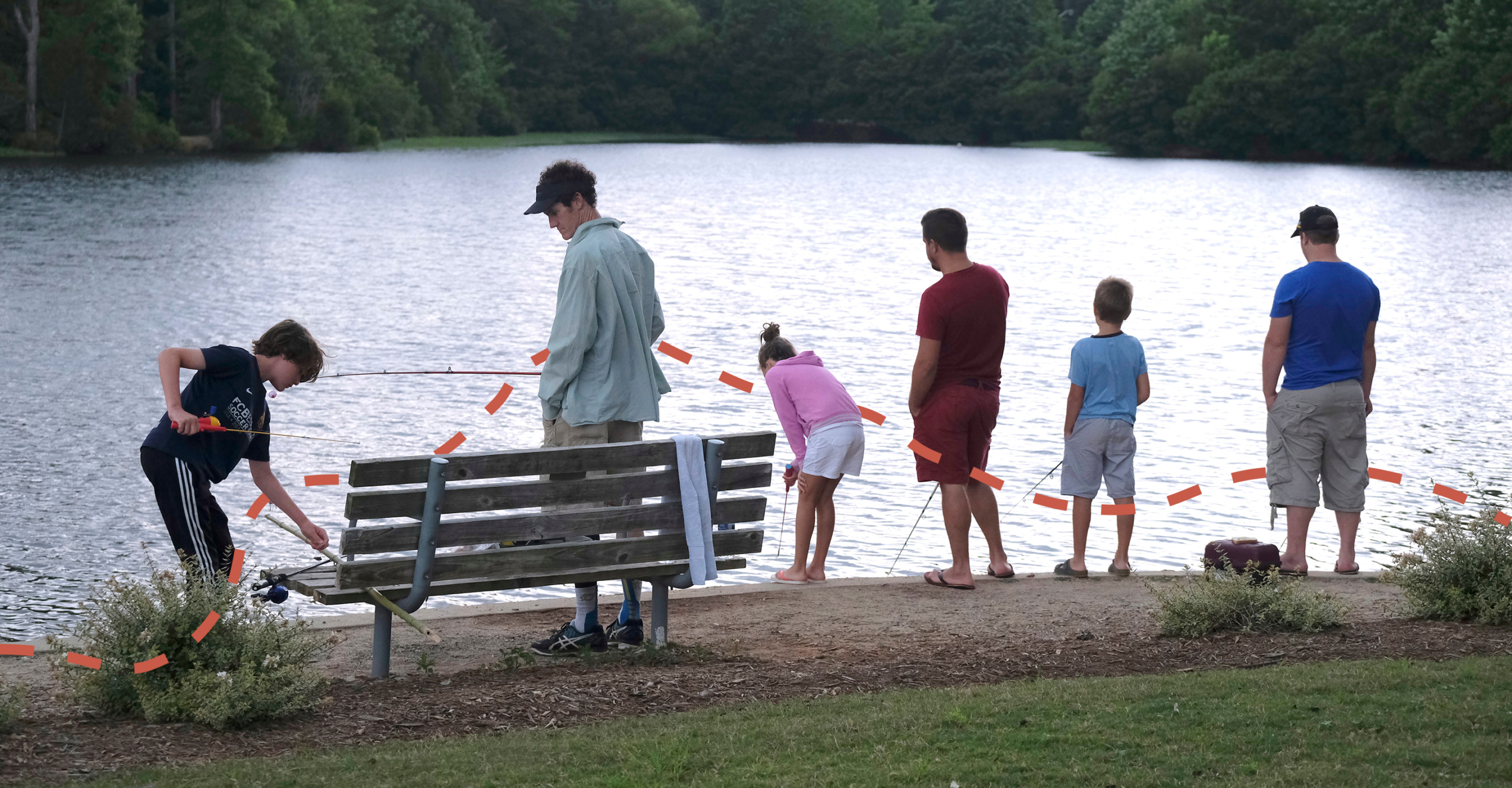 A group of six people fishing at the edge of a small lake.